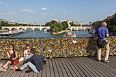 A stroll on the quays of the seine, pont des arts bridge covered in love padlocks, quay of the louvre, paris (75), france