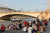 Youths relaxing by the seine on the quay de la tournelle, with a houseboat and the la tournelle bridge, paris (75), france