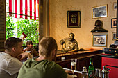 Statue and photos of ernest hemingway (1899-1961), american author and journalist, in the bar el floridita where he drank his favorite daiquiri, calle del obispo, habana vieja, havana, cuba, the caribbean