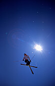 Skier in Sky with Sun Flare