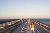 Woman Running on Bridge Over Ocean, Selective Focus, Rear View, Florida Keys, USA