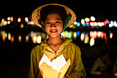 Vietnamese young girl along the river with typical vietnamese conic hat holding a typical lantern with other blurred lanterns light in the background, Hoi An, Vietnam