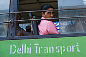 Passenger on a green public transportation bus in Delhi, India