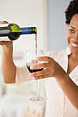 Black woman pouring glass of red wine, Jersey City, New Jersey, USA