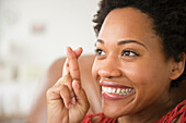 Close up of Black woman smiling with fingers crossed, Jersey City, New Jersey, USA