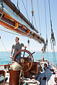 Caucasian man steering sailboat, Cape Town, Western Cape, South Africa