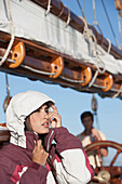 Caucasian woman wearing jacket on sailboat, Cape Town, Western Cape, South Africa