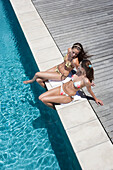 Caucasian women relaxing by swimming pool, Cape Town, Western Cape, South Africa