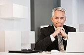Businessman sitting at desk in office, Cape Town, Western Cape, South Africa