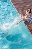 Woman splashing in swimming pool, Palma de Mallorca, Balearic Islands, Spain