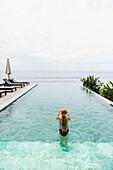 Caucasian girl swimming in infinity pool, Candidasa, Bali, Indonesia