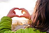 Caucasian girl admiring sunset through hands, Cannon Beach, Oregon, United States