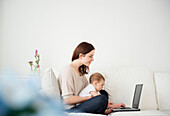 Mother and baby using laptop on sofa, Jersey City, New Jersey, USA
