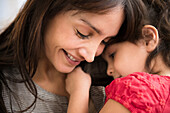 Hispanic girl whispering in mother's ear, Jersey City, New Jersey, USA