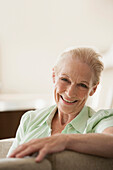 Senior Caucasian woman smiling on sofa, Cape Town, Western Cape, South Africa