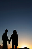Silhouette of Caucasian couple holding hands, Cape Town, Western Cape, South Africa