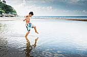 Mixed race boy playing in water on beach, Nayarit, Riviera Nayarit, Mexico