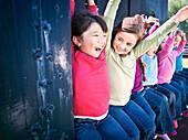 Group of little girls raising hands