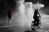 France, Paris at summer, jogger and cyclist under spray along the Seine river