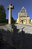 France. Lot. Calvary in the foreground, church in the background of the common Lamothe Fenelon. blue sky