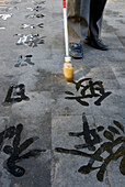 China. Beijing. The Summer Palace. Man Writing Chineese Characters On The Floor With Large Water Brush. Close Up On Characters With Brush And Feet © Eitan Simanor / Axiom
