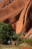 'Tourists walking around Uluru, formerly known as Ayers Rock; Northern Territory, Australia'