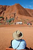 'Tourists watching people climb Uluru, formerly known as Ayers Rock; Northern Territory, Australia'