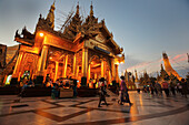 'Visitors walk around Shwedagon Pagoda at sunset; Yangon, Burma'