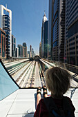 'Young boy sitting at the front of metro train as it travels through the business district of Dubai; Dubai, United Arab Emirates'
