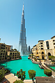 'Looking across large artificial lake to fountain display beneath the Burj Khalifa; Dubai, United Arab Emirates'