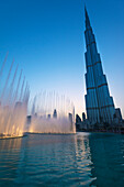 'Fountain display in front of the Burj Khalifa at sunset; Dubai, United Arab Emirates'