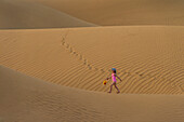 'Girl in pink swimsuit with bucket and spade walking across sand dunes at dusk; Dubai, United Arab Emirates'
