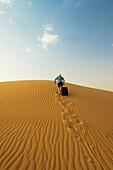 'Barefoot man with suitcase walking up sand dune; Dubai, United Arab Emirates'