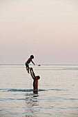 'A father standing in the water and throwing his son into the air; Puglia, Italy'