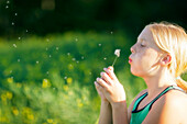A Young Girl Blowing Dandelion Seeds In The Breeze