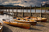 'Lake District, Cumbria, England; Four Rowboats On Shore'