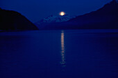 'Taiya Inlet, Skagway, Alaska, United States Of America; A Moon Over The Chilkat Mountains In The Lynn Canal Of The Inside Passage'