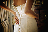 A Woman Fastening The Back Of Her Wedding Dress