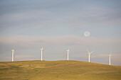 'Pincher Creek, Alberta, Canada; Wind Turbines On A Hillside With The Moon In The Sky'