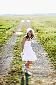 A Bride Standing On A Dirt Road In A Field