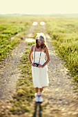 A Woman In A White Dress Standing On A Dirt Road With A Camera Around Her Neck