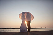 Silhouette Of A Bride And Groom Behind An Umbrella