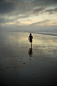 A Person Running On The Beach At Sunset