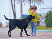 'Benalmadena, Malaga, Andalusia, Spain; A Young Girl Walks With Her Dog'