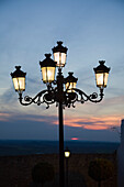 'Medina Sidonia, Andalusia, Spain; A Light Post With 5 Lamps On It Illuminated At Night'