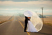'Bride And Groom In An Embrace Standing On A Road In Rural Alberta; Three Hills, Alberta, Canada'
