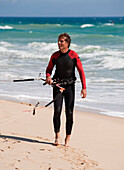 'A Man On Punta Paloma Beach Wearing A Wetsuit And Carrying Kitesurfing Equipment; Tarifa, Cadiz, Andalusia, Spain'