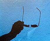 'Shadow Of Hand Holding Eyeglasses Against A Blue Wall; Tarifa, Spain'