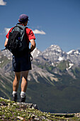 'Male Hiker Standing On Top Of A Ridge Overlooking A Mountain Valley; Alberta, Canada'