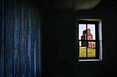 'A Grain Elevator Seen Through The Window Of An Old, Abandoned Ghost Town Store; Bents, Saskatchewan, Canada'